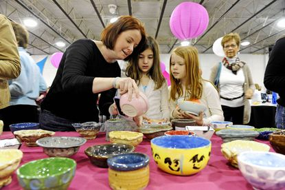 Amy Dibari, Lucy Delgaudio, 8, and Kathryn Dibari, 8, browse through bowls donated by professional and amateur potters at Empty Bowls, St. Vincent de Paul's fundraiser to benefit the city's hungry and homeless.