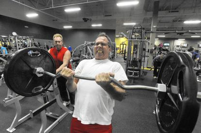 John Bosley watches John Trinite curl 125 pounds at Gold's Gym in Westminster.