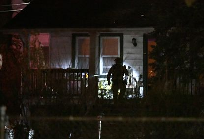 A police officer checks front porch as the barricade situation in Woodlawn nears conclusion on April 7, 2021.