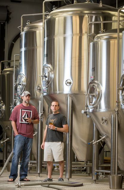 Jailbreak Brewery co-founders Justin Bonner, left, and Kasey Turner, next to brew kettles at their North Laurel brewery.