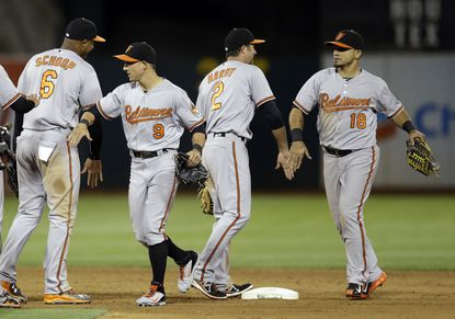 From left, Orioles Jonathan Schoop, David Lough, J.J. Hardy, and Gerardo Parra celebrate their 9-2 win over the Oakland AthleticsonMonday, Aug. 3, 2015, in Oakland, Calif.