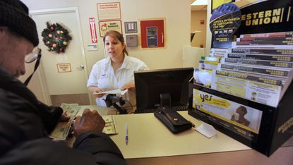 Jenny Lawless, of South Bethlehem, Pennsylvania, a grocery store employee, assists customer Frank Becker as he makes a Western Union transaction in 2011. She previously spotted a scam and refused to allow an 84-year-old man to wire more than $5,000 from the store's Western Union counter. File. (Monica Cabrera/The Morning Call).