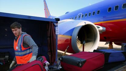 Southwest Airlines baggage handlers load suitcases onto an airplane bound for Orlando, Fla., while it's at its gate Oct. 8, 2014, at Midway International Airport in Chicago.