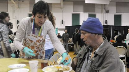 Volunteer Lou Ann Jasper serves guest Michael Warden, of Belcamp, during Hope in Action's eighth annual community Thanksgiving dinner at the Bel Air Armory Sunday afternoon.