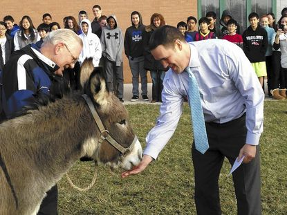 Burleigh Manor Middle School students and staff watch as principal John DePaula gets friendly with Jenny the donkey prior to giving it a kiss.
