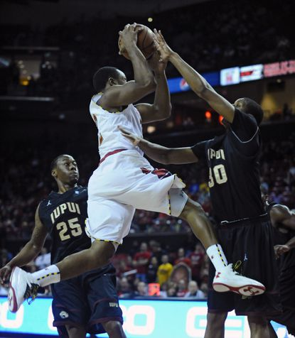 Maryland's Dez Wells drives to the basket against IUPUI's Donovan Gibbs (right) in the first half.