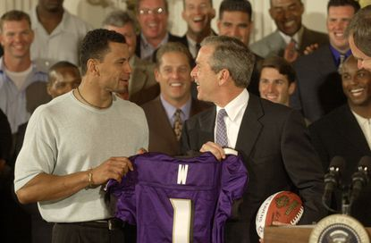 President George W. Bush is presented with a football and Ravens jersey by safety Rod Woodson. The team was on hand to accept congratulations for winning Super Bowl XXXV.