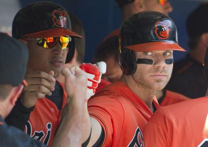 Orioles first baseman Chris Davis is congratulated in the dugout after hitting a two-run home run in the fourth inning of a baseball game against the Toronto Blue Jays in Toronto, Saturday, June 11, 2016.