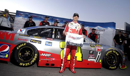Jeff Gordon poses for photos after winning the pole position for Sunday's NASCAR Sprint Cup Series auto race in Las Vegas.
