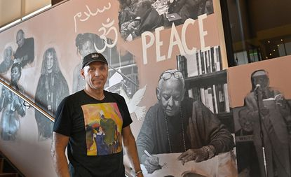 """Busboys and Poets owner, Andy Shallal, stands in front of a portion of the mural he is creating themed, """"I Dream A World"""" by Harlem Poet 1941 Langston Hughes. Soon to open in Columbia (Oct. 10) is the largest location of """"Busboys and Poets."""" Owner Andy Shallal creates the unique mural at each of his locations."""