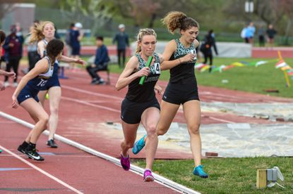 Senna Ohlsson takes a handoff from Molly Smith (right) in a 4x400-meter race at the Loyola/Johns Hopkins Track and Field Complex in the Loyola/Johns Hopkins Invitational on April 12, 2019.