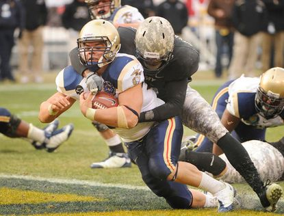 Navy fullback Eric Kettani (left) carries a defender into the end zone as he scores in the second half of the 109th meeting against Army.
