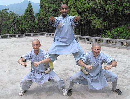 Westminster graduate Rick Gavigan, right, and Cale Klesko, left, participate in a posed photograph at a Shaolin Temple in China.