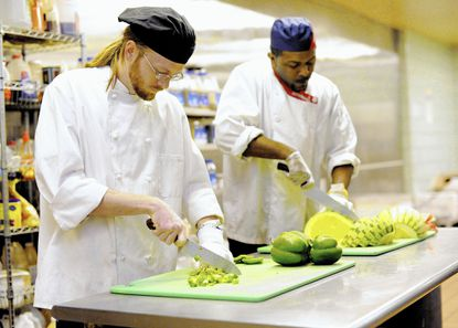 Mike O'Brien, left, and Walter Hill-El prepare locally sourced peppers and melons in the cafeteria at McDaniel College in Westminster Wednesday, Oct. 22. McDaniel College pledged Wednesday to purchase twenty percent of food from local, sustainable, humane and fair-trade sources by 2020.