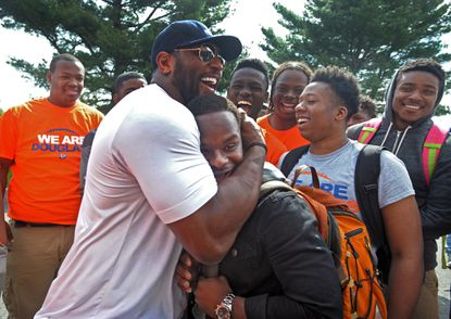 Former Baltimore Ravens star Ray Lewis hugs Azariah Bratton-Bey Jr., 17, a senior running back on Frederick Douglass High's football team in Baltimore, as Ravens players, coaches and staff visit schools on Thursday, April 30, 2015, to provide positive support as protests continue following the recent death of Freddie Gray while in the custody of Baltimore police. (Kenneth K. Lam/Baltimore Sun)