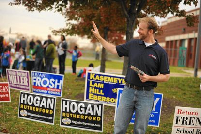 State delegate candidate Tom Coale waves to voters as they arrive at Ilchester Elementary School on Tuesday, November 4.