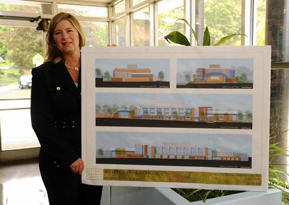 Waverly Elementary/Middle School Principal Michelle Ferris shows the design drawings for a $25 million replacement school in June, when ground was broken for the project.