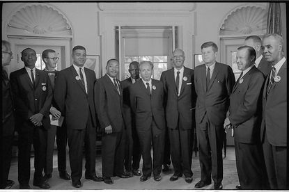 Civil rights leaders meet with President John F. Kennedy in the oval office of the White House after the March on Washington in 1963. Photograph shows (left to right): Willard Wirtz (Secretary of Labor); Floyd McKissick (CORE); Mathew Ahmann (National Catholic Conference for Interracial Justice); Whitney Young (National Urban Leage); Martin Luther King Jr.(SCLC); John Lewis (SNCC); Rabbi Joachim Prinz (American Jewish Congress); A. Philip Randolph, with Reverend Eugene Carson Blake partially visible behind him; President John F. Kennedy; Walter Reuther (labor leader), with Vice President Lyndon Johnson partially visible behind him; and Roy Wilkins (NAACP).