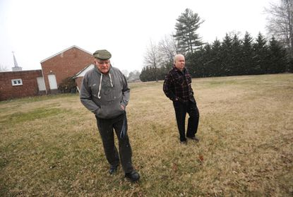 Roger Copinger, left, and Russ Harrington walk the grounds of the Church of the Ascension.