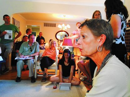 Lisa Van Bavel listens during a meeting Thursday of Overbrook residents to discuss their options for solving flooding problems in the community. The gathering was held at the home of Kristin Kluga, who is standing second from right. Seated at left, taking notes, is David Marks, a Baltimore County councilman who represents the Towson area.