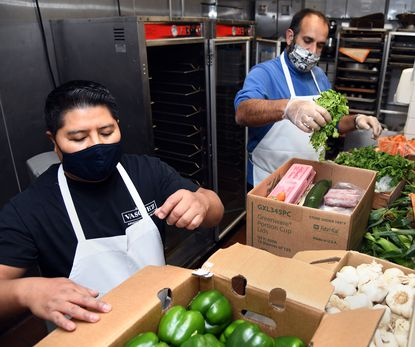 Chef Mario Cano Catalan, left, executive chef at Bar Vasquez, and Patrick Del Valle, general manager of Petit Louis, pack food boxes for employees of the Foreman Wolf Restaurant Group.