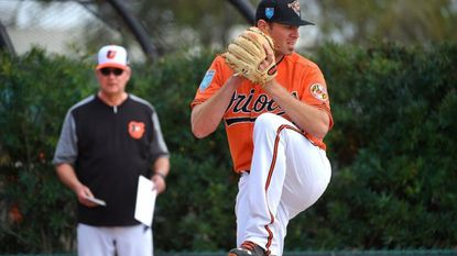 Chris Tillman is watched by pitching coach Roger McDowell, while he throws during his pitching session. Baltimore Orioles' Spring Training at the Ed Smith Stadium complex in Sarasota, Florida.