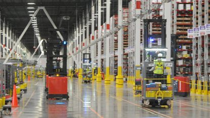 Amazon workers operate 'order pickers' in the company's Cecil County distribution center Friday. State, federal and local leaders were given a tour of the facility as part of a grand opening celebration.