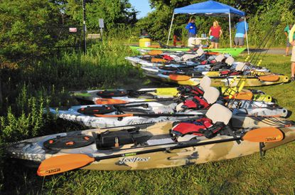 These beamy kayaks with scuppers are designed for stability. Each is equipped with a tackle box for the day's fishing, a rod with an overboard float, a kayak floatation vest and a paddle with a tether. Under the canopy, volunteer, Melissa Sealsky, a recreational therapist at Franklin Square Hospital, registers participants and collects releases and any photo restriction requests.