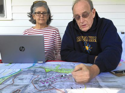 Haviland Mill Road neighbors Brooke Farquhar, left, and John Newhagen, look at a plan for development on a former farm down the street.