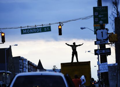A performer named Dimitri Reeves dances and sings Michael Jackson songs on the roof of a truck on North Avenue in Baltimore, Monday, April 27, 2015, amid Freddie Gray protests.