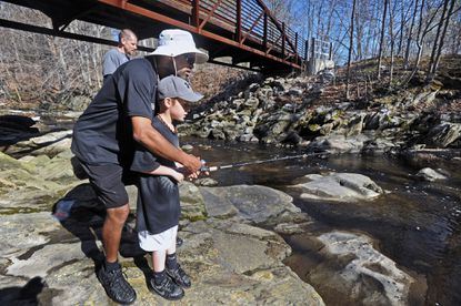 Volunteer Tony Brown, center, of Owings Mills, teach Damion Denkowski, 9, of Baltimore, fish for trouts stocked by Trout Unlimited. Maryland Trout Unlimited hosted about 70 kids and their families on its annual City Catch at Leakin Park on April 18. The group provided fishing rods and guides to teach them fishing techniques and instill some sense of conservation ethic.