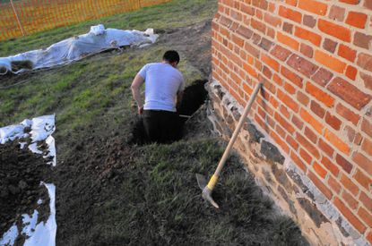 An Oak Grove Restoration worker hand digs a 3-foot wide, 3-foot deep trench around the exterior foundation in 2013 as part of the moisture abatement project. Almost all trenching for the restoration project was done by hand so that archaeologists monitoring the work could access and document any archaeological artifacts discovered.