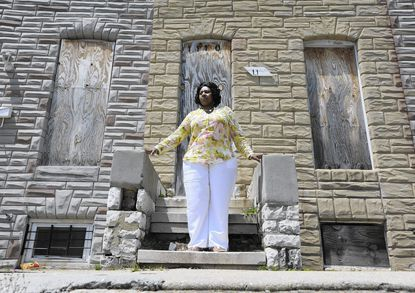 Kimberly Smith, mother of Cecil Harris, who has lead poisoning, is is pictured in front of the house, where she says he was poisoned during a study when she lived there.