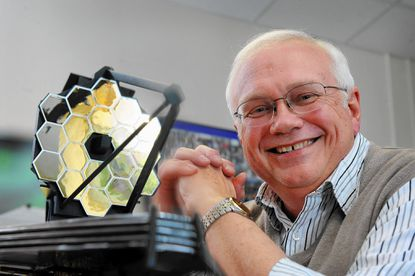 Bill Ochs, project manager of the James Webb Space Telescope at NASA Goddard, shows a model of the telescope.