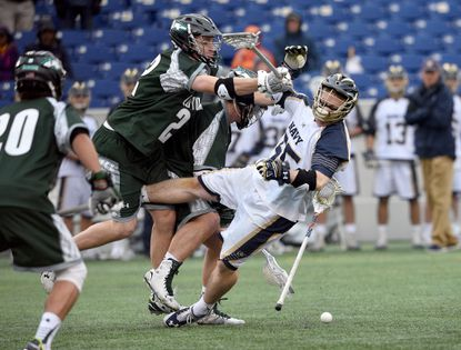 Loyola's Jack Carrigan sends Navy face-off man Brady Dove to the turf during a game in 2016.