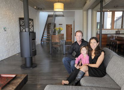 The Currey family sit in the great room of their dream home that was once a store in Locust Point. Left to right: Chris, Neila, 5, and Isabel.