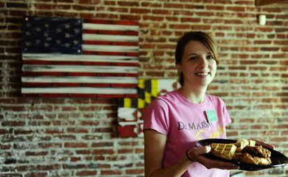 Jackie Carneal, a hostess at DelMarVa Southern Cafe on Boston Street, holds the Golden Tenders and Waffle platter.