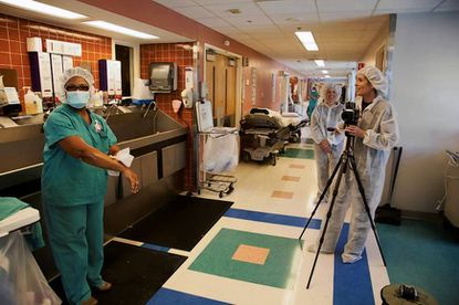 "Nurse Germaine Williams shows Carolyn Jones and producer Lisa Frank how to ""scrub in"" outside the Johns Hopkins Hospital."