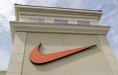 In this file photo dated Tuesday, Sept. 4, 2018, a Nike company logo is displayed outside a Nike store in Charlotte, North Carolina. Nike is one of 55 major U.S. companies recently named in a report for not paying any federal income tax on billions of dollars in profits. (AP Photo/Chuck Burton, FILE)