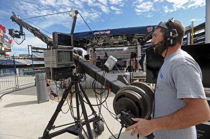 Boom camera operator Jon Mancini checks his camera in preparation for the pregame show broadcast during a Nationals baseball game.