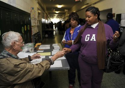 """Baltimore's spending board on Wednesday approved a $633,000 plan to train thousands of election judges ahead of February's special primary for the late Rep. Elijah Cummings' 7th Congressional District seat. In this file photo, an election judge hands """"I Voted"""" stickers to voters at Northwood Elementary School."""