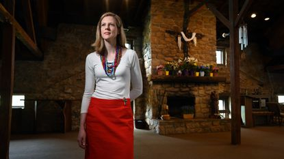 The Rev. Claire Matheny stands inside Kittamaqundi Community Church. The church, located in a former carriage house where thoroughbreds were kept, is celebrating its 50th anniversary this year.