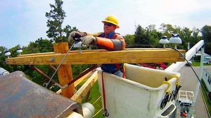 Lineman Shane McCarty of Pike Electric (Alma, Ga.) connects high voltage wires together.