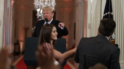 President Donald Trump berates CNN correspondent Jim Acosta as a White House aide attempts to take away a microphone from the journalist during a news conference in the East Room of the White House on Nov. 7.
