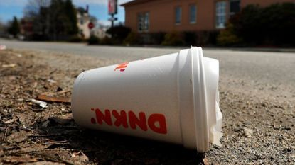 A coffee cup made from polystyrene foam, commonly known as Styrofoam, lies on the side of a road in Augusta, Maine.