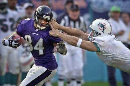 Ravens receiver Jermaine Lewis gets tackled by the facemask as Miami punter Matt Turk hangs on to make the tackle in 2002.