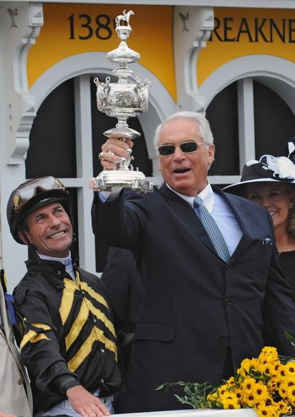 D. Wayne Lukas, trainer of Preakness winner Oxbow, hoists the winner's trophy for the sixth time at Pimlico Saturday, where he also captured his 14th victory in a Triple Crown Series race, an all-time record. Winning jockey Gary Stevens is to his right.