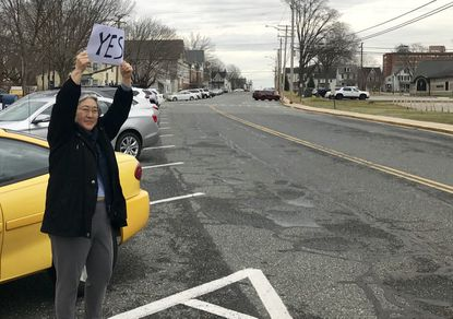 May Kuroiwa, of Havre de Grace, stands on Pennington Avenue near City Hall Tuesday, holding a sign encouraging people to vote in favor of a $15 million city bond referendum, allowing the city to borrow money to fix aging water and sewer infrastructure.