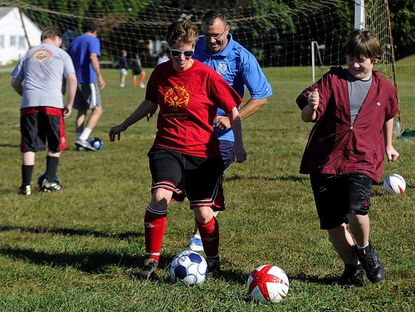 From left, Shelley Bowling, coach Bob Ballard and Seth Watters run a drill during practice in Westminster Saturday. Bowling is a member of the Carroll County Special Olympics soccer team that will be going to the National Games in New Jersey next summer.