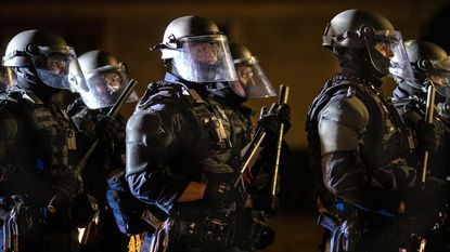 Portland police take control of the streets after making arrests on the scene of the nightly protests at a Portland police precinct on Sunday, Aug. 30, 2020 in Portland, Ore. President Donald Trump and the city's mayor have argued publicly over who was to blame for the violence. (AP Photo/Paula Bronstein)